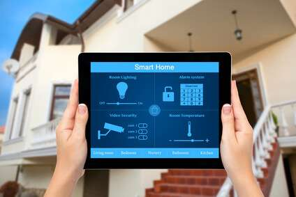 Female hands hold a tablet computer with system smart house on a screen on the background of the house