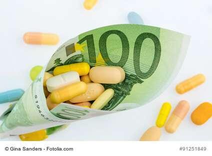 Tabletten und einhundert Eurogeldschein Symbolfoto: Kosten für Medizin und Medikamente der Pharmaindustrie