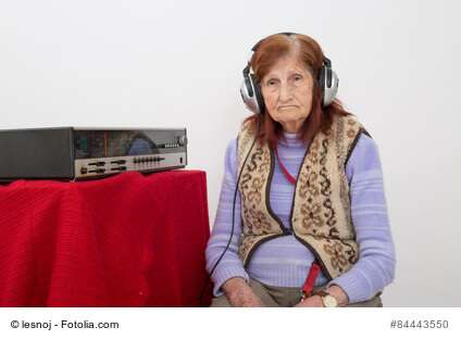 Elderly lady listening to the radio.