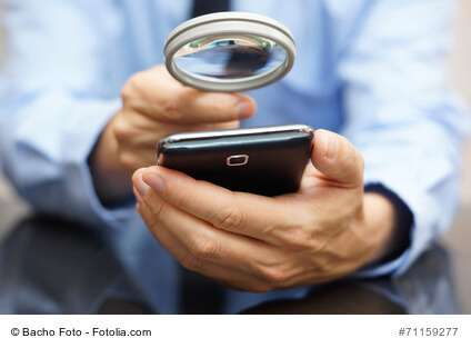 Businessman using mobile smart phone with magnifying glass . Phone fraud concept