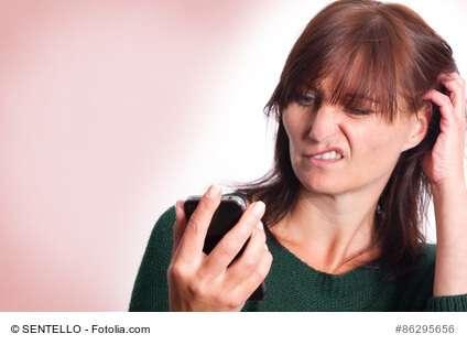 Frau versteht Smartphone nicht und kratzt sich am Hinterkopf